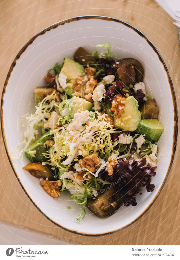 Gourmet salad of avocado, walnuts, tomato and green sprouts. Served in a fancy restaurant vitamin recipe colorful cucumber balsamic eat cheese dressing onion