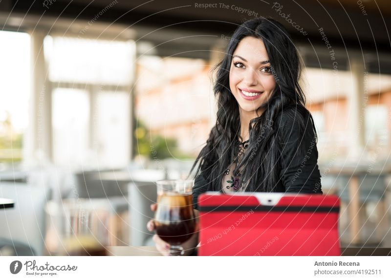 Pretty dark haired woman looking at camera and drinking coke young attractive 20s joy people person youth urban women pretty pretty people relaxing