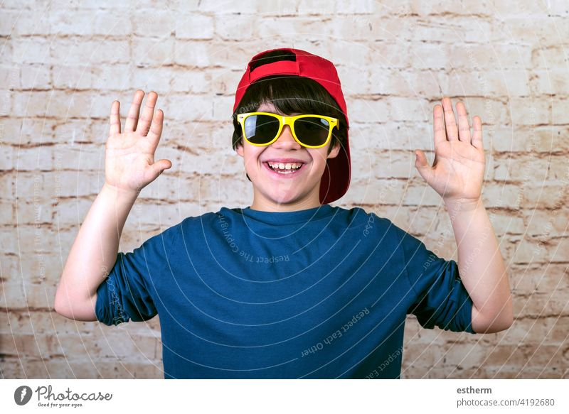 happy and smiling boy with cap and sunglasses showing palms of hands accessory kid happiness caucasian fashionable lifestyle summer childhood modern holidays