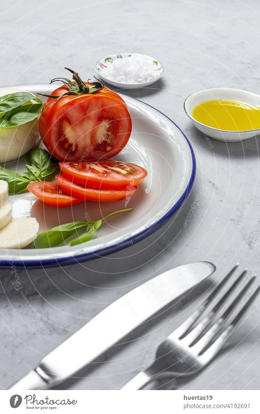 Homemade Italian caprese salad with sliced tomatoes, mozzarella cheese, basil and olive oil food mediterranean italian plate background fresh healthy olive il