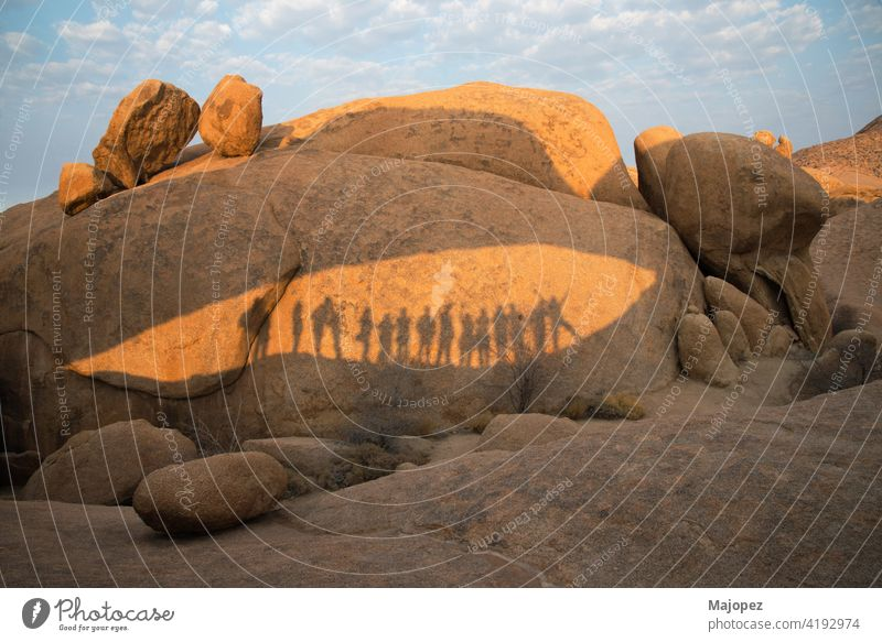 Rocks at Damaraland with the shadows of a group of people on a sunny day Namibia enjoy happy together desert hot sky friends rocks orange sunset holidays