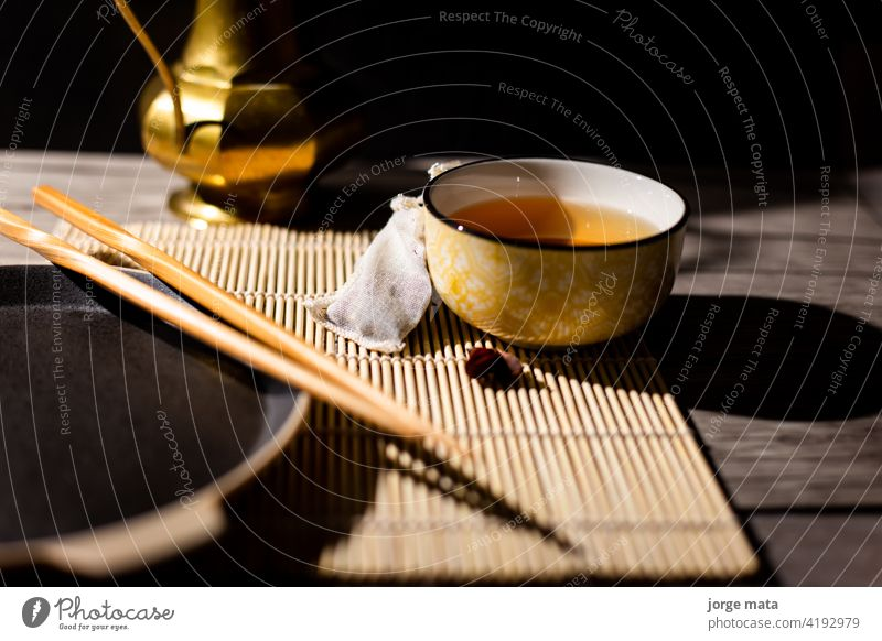 Dark tea background with cup of hot tea on the table. Copy space for your design. Authentic vintage style. Traditional tea ceremony arrangement chinese tea