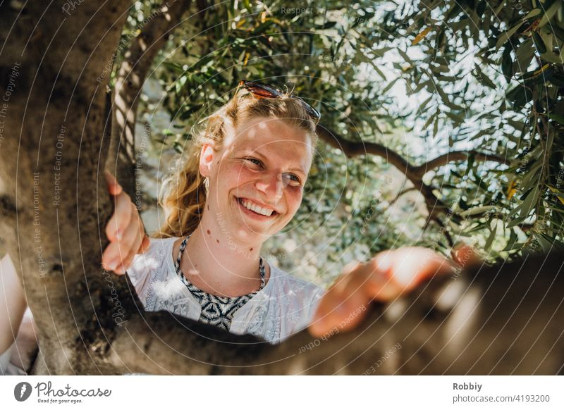 Smiling young woman under olive tree Olive tree Young woman Blonde Sun Sunlight Tree portrait pretty vacation Summer Summer Feeling Exterior shot Colour photo