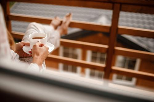 young woman in stylish nightwear enjoy drinking coffee or tea outdoor on balcony in the morning and looks at the mountains. girl holding cup hot summer relax