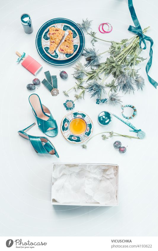 Female lifestyle flat lay with blue new high heels shoes, bouquet of flowers, a cup of tea, cakes, jewelry, cosmetics, empty box, fruits on white desk . Top view. Beauty and fashion concept