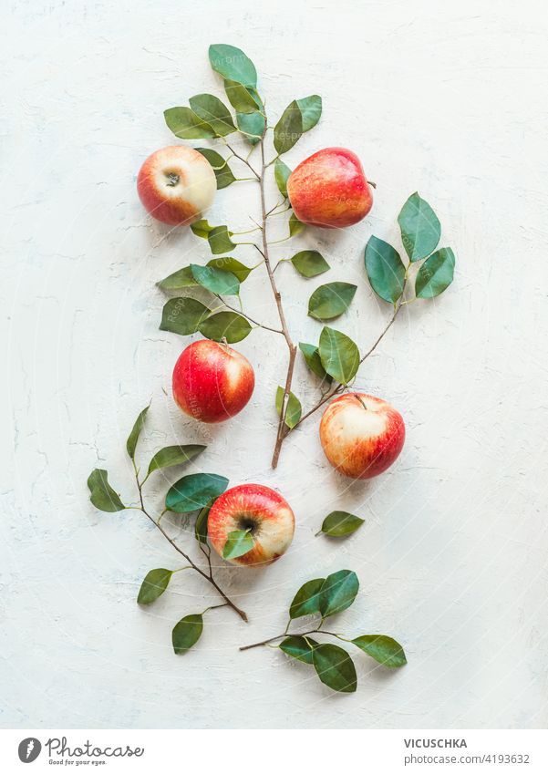 Composition of fresh red apples with green leaves on white desk background. Top view. Flat lay composition top view flat lay branch ingredient group leaf food