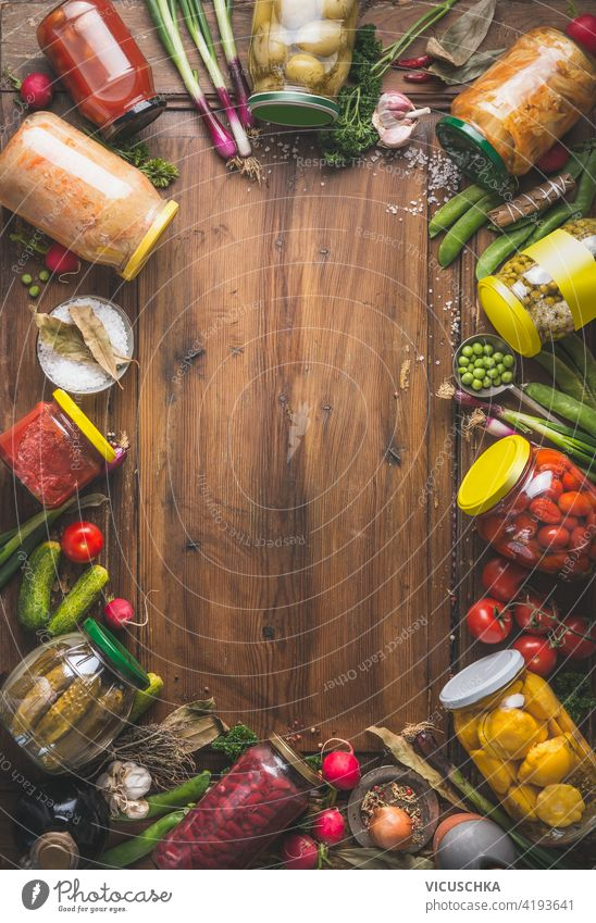 Frame of various pickled colorful vegetables in jars on wooden background with ingredients, herbs and spices. Top view. Copy space. Mock up. Harvest preserving. Fermented  food. Canned vegetables