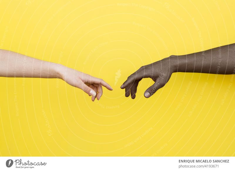 White hand and black hand about to touch on yellow background people friendship together clasped african international relationship skin unity copy space male