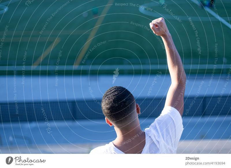 Young man celebrating victory on bleachers watching football arms raised goal winner male soccer soccer staduim black leisure audience sport success athletic