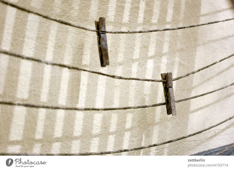 Two clothespins again Holder two Pair duo Duet clothesline Cotheshorse Empty Household Light Shadow Wall (building) leash Side by side Wood Old Weathered