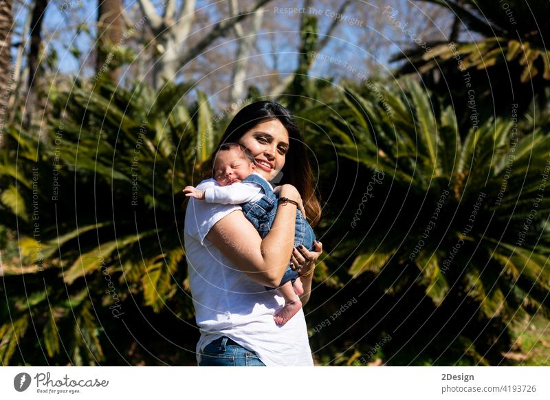 Loving mother with her newborn baby on her arms. child outdoor person family love holding woman lifestyle mom motherhood parent beautiful infant together