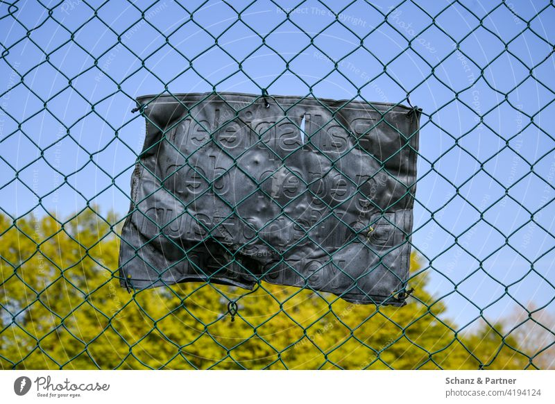 dented tin sign on chain link fence Wire netting fence Fence Tin Dented Signage Warning label DISREGARD Disrespect forbidden amateur football field trees warped