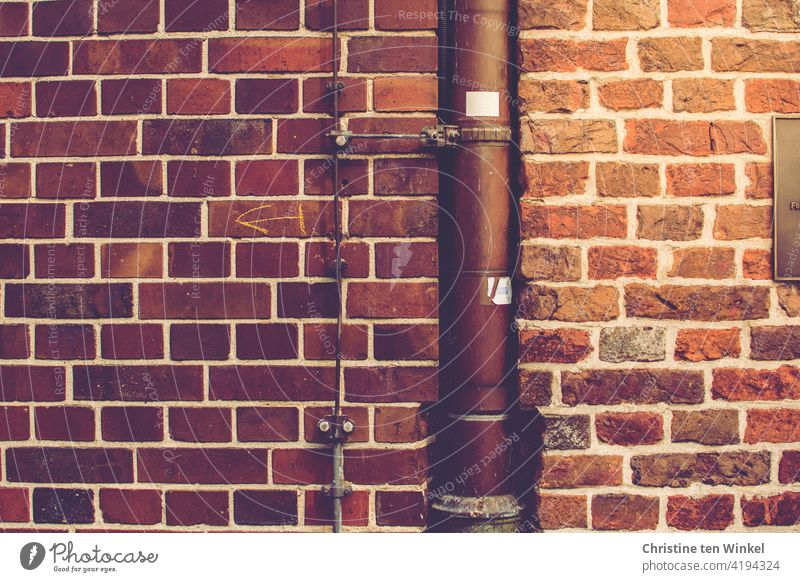 A downpipe and a lightning conductor in the wall at the transition between two brick walls on an old building Downspout Brick wall Wall (barrier) Old Facade