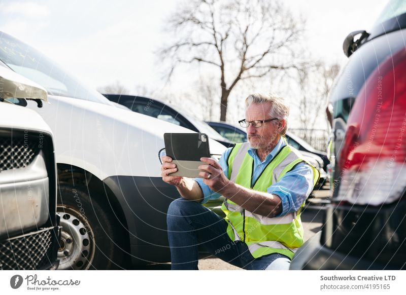 Male Loss Adjuster Taking Photo On Digital Tablet To Assess Insurance Claim In Car Pound car accident wreck crash loss adjuster insurance claim auto damage