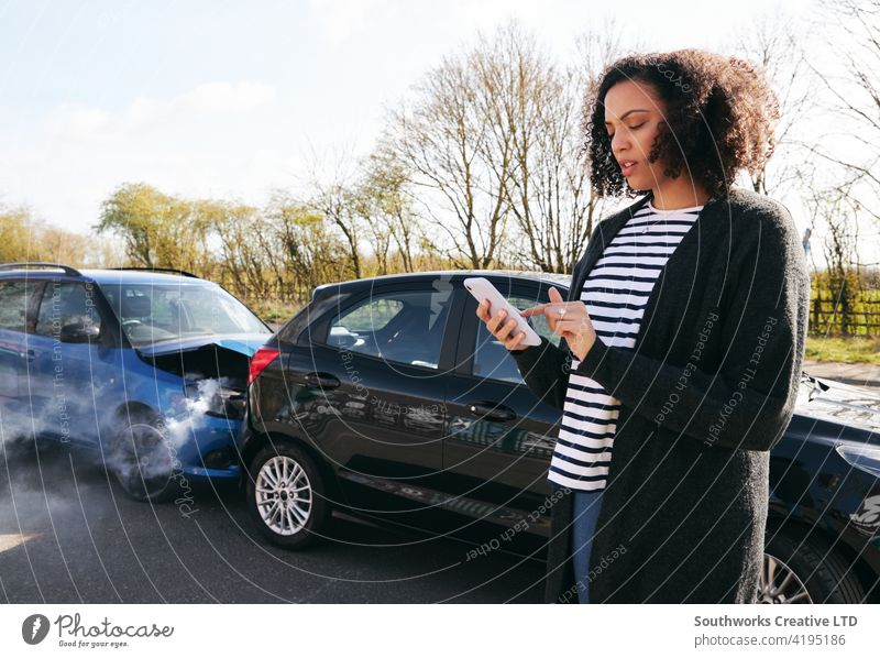 Female Driver Contacting Car Insurance Company On Mobile Phone After Road Traffic Accident woman driver car accident wreck crash insurance claim calling