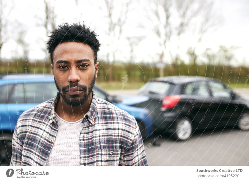 Portrait Of Uninsured Male Driver At Fault After Road Traffic Accident man driver car accident wreck crash portrait looking at camera uninsured fault blame