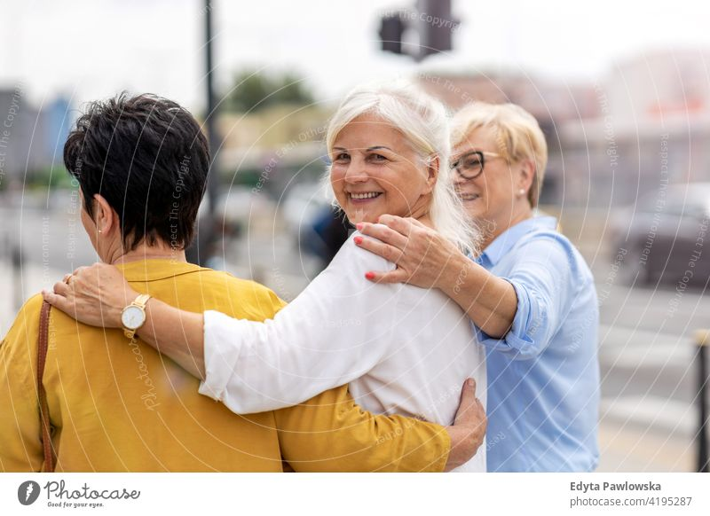 Senior female friends having good time together senior woman people retired retirement grandmother leisure standing confident attractive urban city street