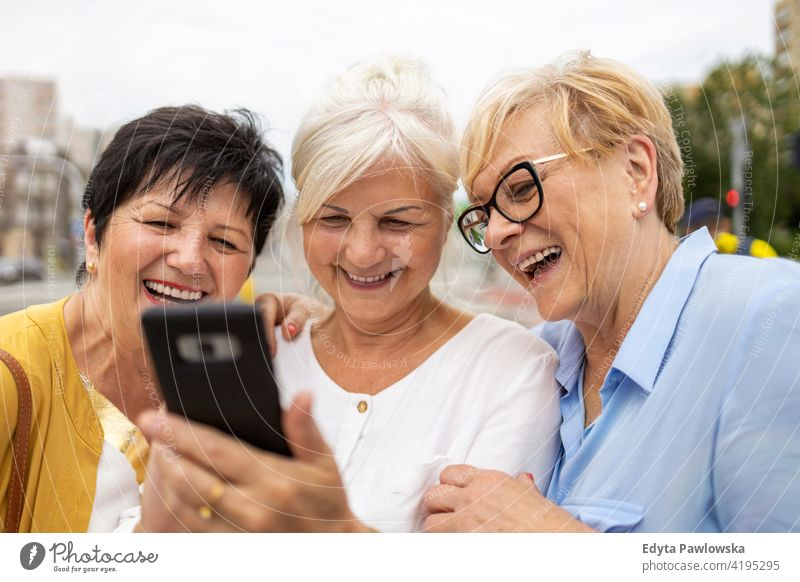 Group of senior women using smartphones together woman people retired retirement grandmother leisure standing confident attractive urban city street beautiful