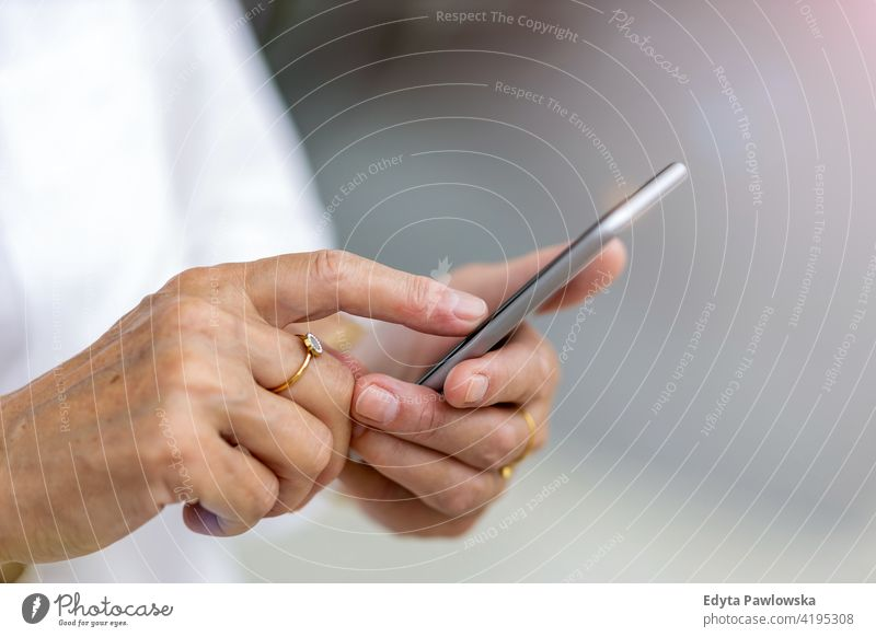 Senior woman's hands holding a smart phone mobile phone smartphone senior app people retired retirement using phone age pensioner aged person elderly adult