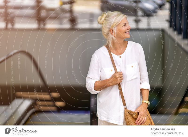 Portrait of senior woman smiling in the city people retired retirement leisure standing confident attractive urban street positive joy enjoyment cheerful happy