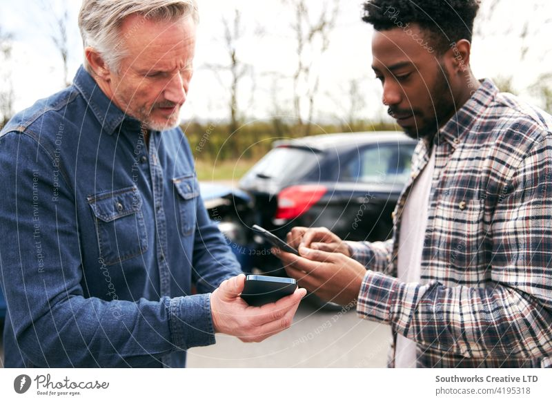Senior Male Driver Exchanges Car Insurance Details With Younger Motorist After Road Traffic Accident men man driver car accident wreck crash insurance claim