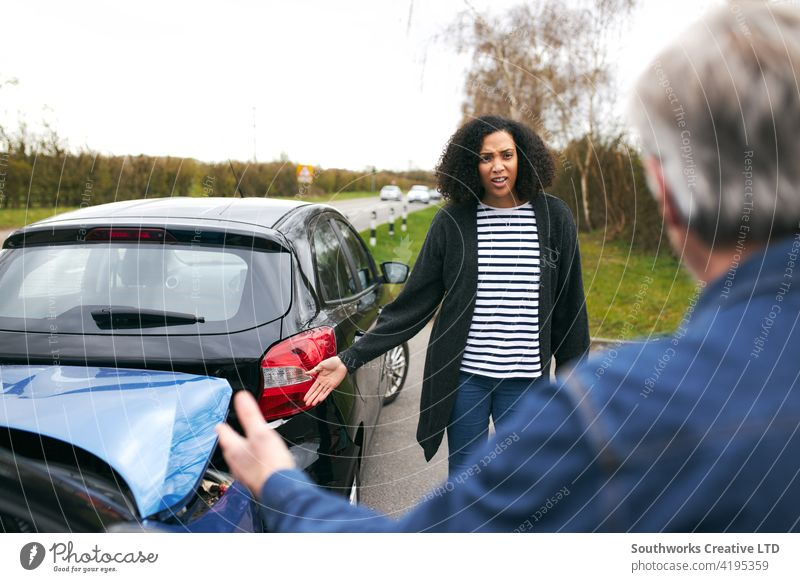 Senior Male Driver Arguing Over Blame For Car Accident With A Younger Female Motorist woman driver car accident wreck crash insurance claim arguing argument