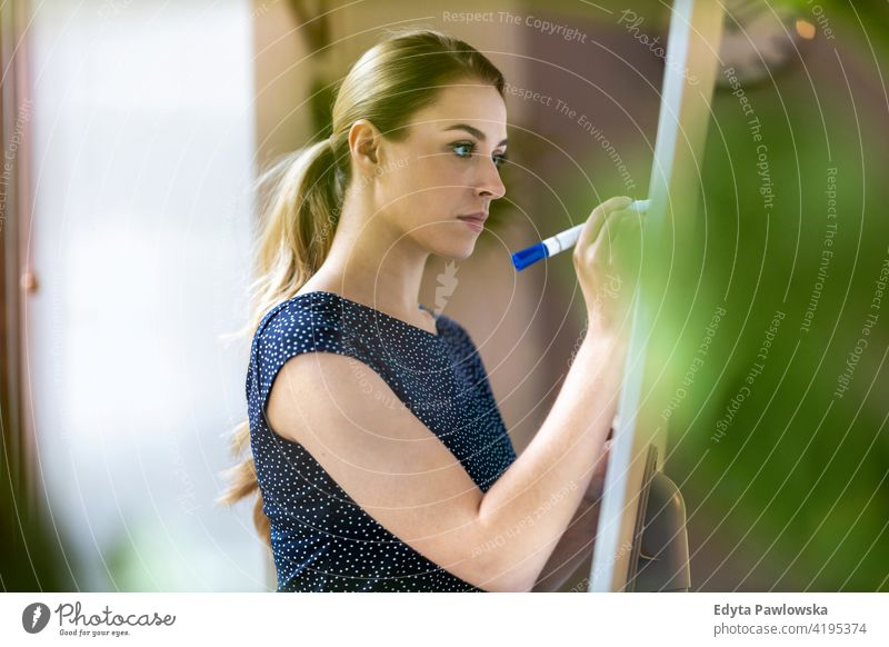 Young businesswoman writing on white board with her marker pen in office girl people Entrepreneur successful professional young adult female lifestyle indoors