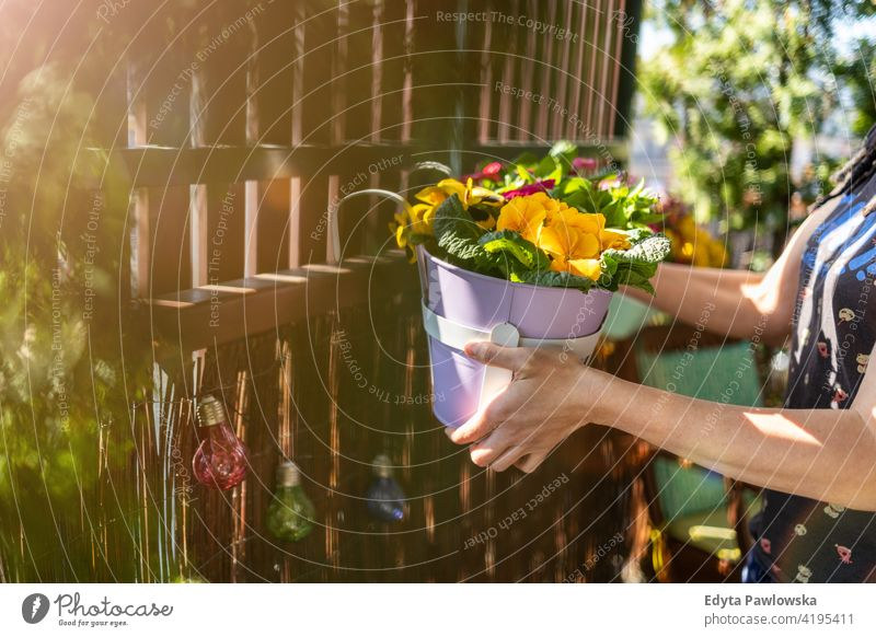 Young woman taking care of her plants on the balcony holding hands colorful blooming fresh floral decoration blossom beautiful hobby florist pot natural person