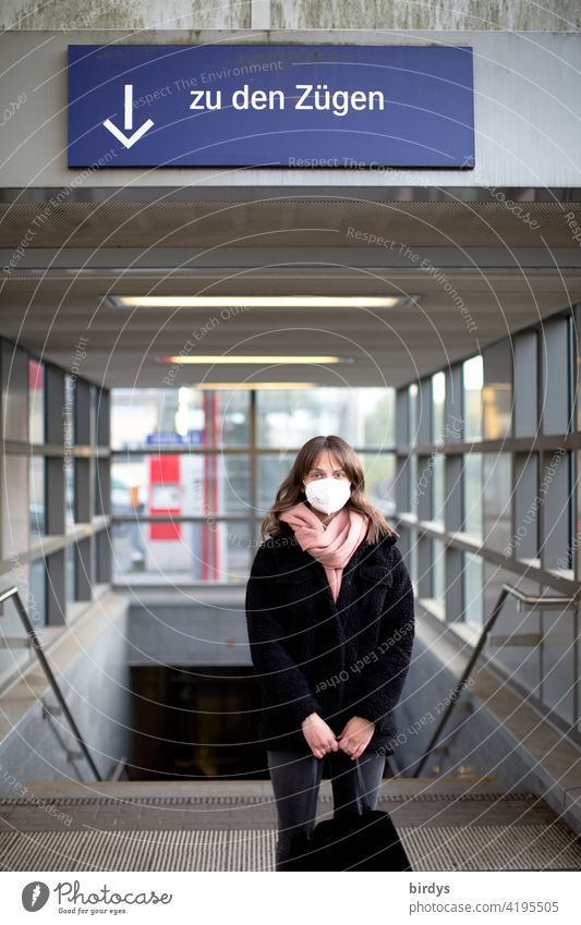 A young woman with FFP2 - mask stands at the station in front of the stairs to the tracks, trains. Mask obligation Train station German Federal Railway db ffp2