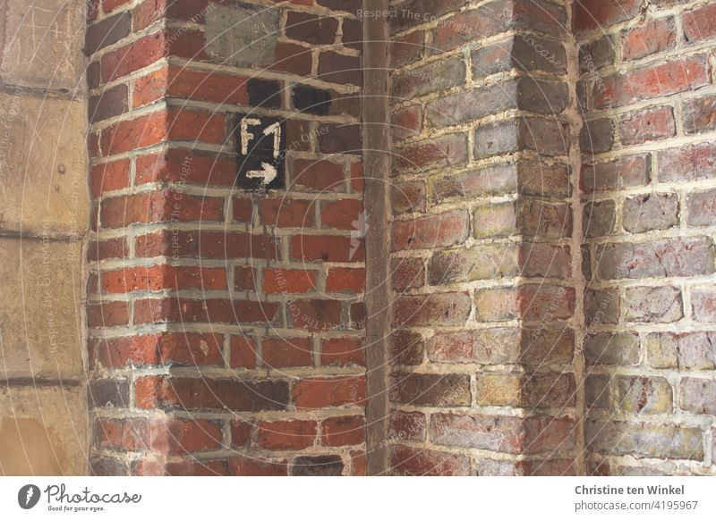 Signpost F1 with arrow pointing to the right in the corner of a building where several old brick and sandstone walls meet Road marking sign Arrow