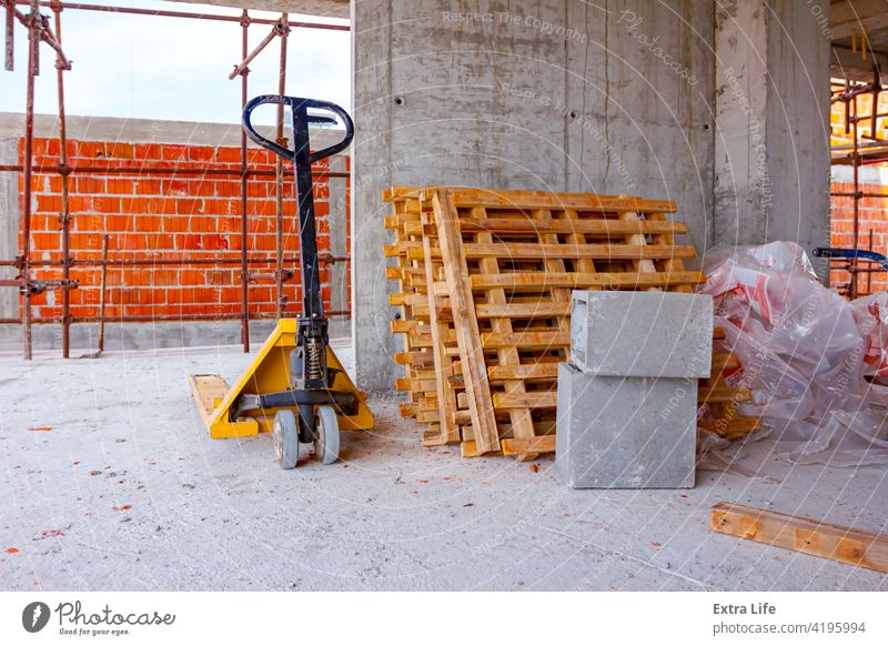 Pedestrian stacker and piled wooden pallets placed against the wall in background Against Architecture Arranged Block Building Site Bunch Cargo Carry Cement
