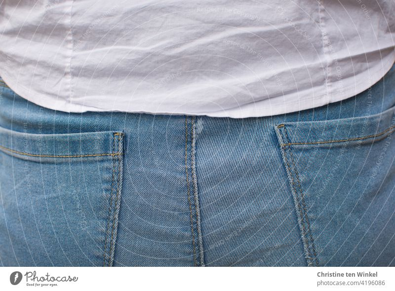 Back view of a young woman in light blue jeans and white blouse. Detail view. bottom Blouse Rear view Jeanspo Adults 1 Woman Youth (Young adults) Young woman