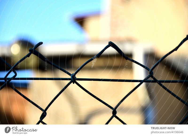 Because the focus is on the wire mesh fence, one does not realize that the building in the bright sunlight is a dilapidated workshop, especially since the blue sky reinforces the positive mood.