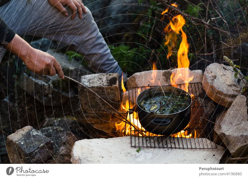 Friends camping eating food concept. A warm fire you to drink and camp in the mountains bonfire burn campfire cook flame heat hot nature outdoor picnic travel