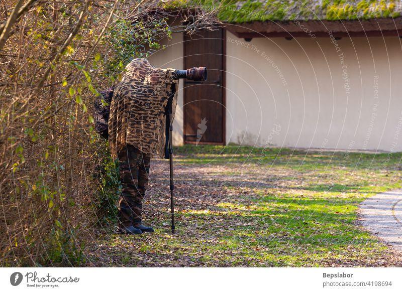 Bird photographer wearing camouflage cape nature camera photography photographing blend blending laguna di marano bird photographer concealment photographic