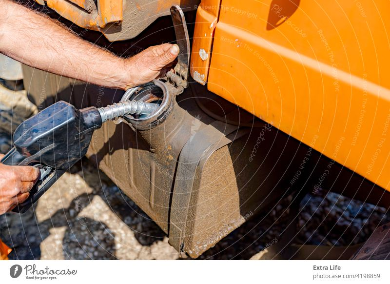 Hand holding handle fuel nozzle to refuel, petrol is pouring into the tank of an industrial mechanization Activity Barrel Building Site Bulldozer