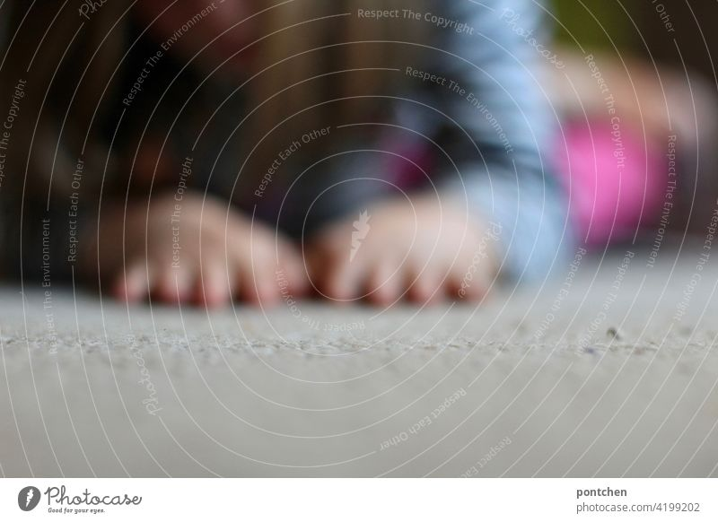 Child playing on the floor. Blurred child hands Lie Carpet Playing blurriness Living or residing Life Crawl