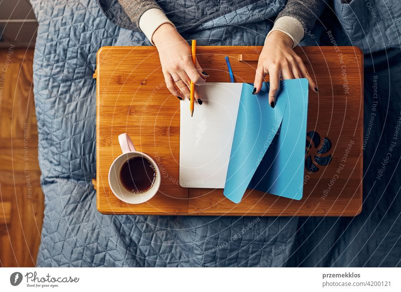 Young woman opening diary, writing journal. Making notes in diary sitting in bed education indoor learning student working person female notebook studying