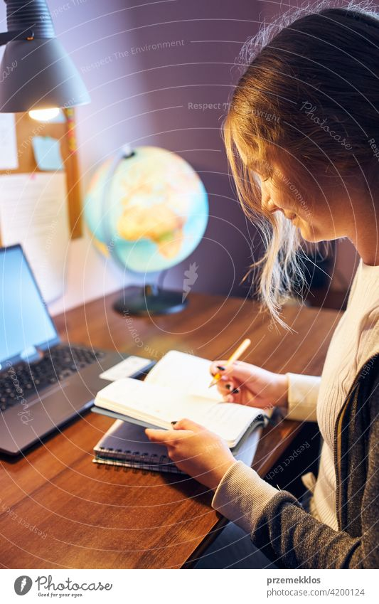 Student learning remotely from home. Young woman having classes online, making notes, reading and learning sitting at desk education indoor student working