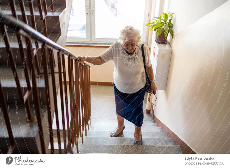 Senior woman climbing staircase with difficulty people senior mature casual female Caucasian elderly home house old aging domestic life grandmother pensioner