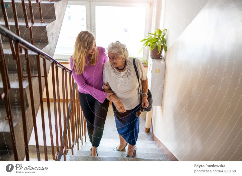 Caregiver helping senior woman climb staircase people mature casual female Caucasian elderly home house old aging domestic life grandmother pensioner