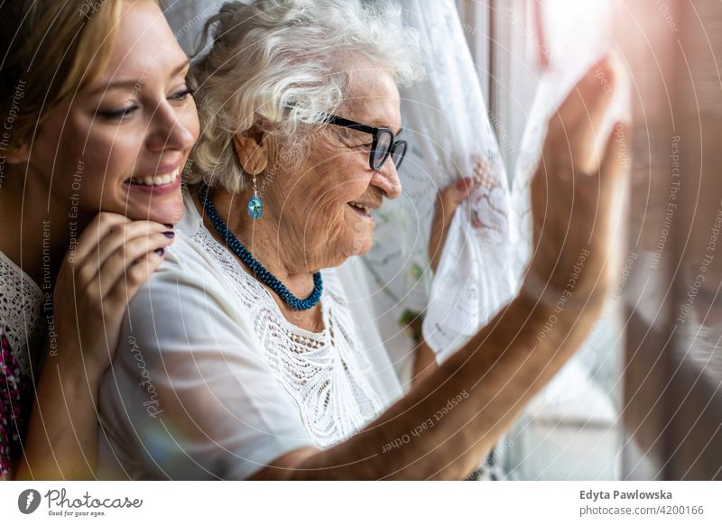 Young woman spending time with her elderly grandmother at home people senior mature casual female Caucasian house old aging domestic life pensioner grandparent