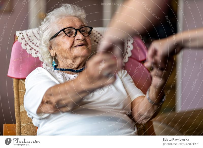 Female home carer supporting old woman to stand up from the armchair at care home people senior mature casual female Caucasian elderly house aging domestic life