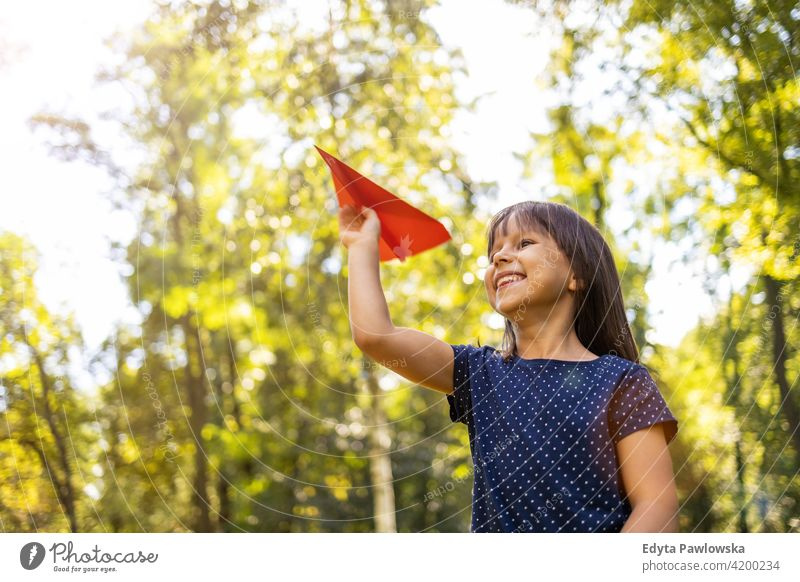 Little girl playing with paper plane in park people child little girl kids childhood outdoors casual cute beautiful portrait lifestyle elementary leisure