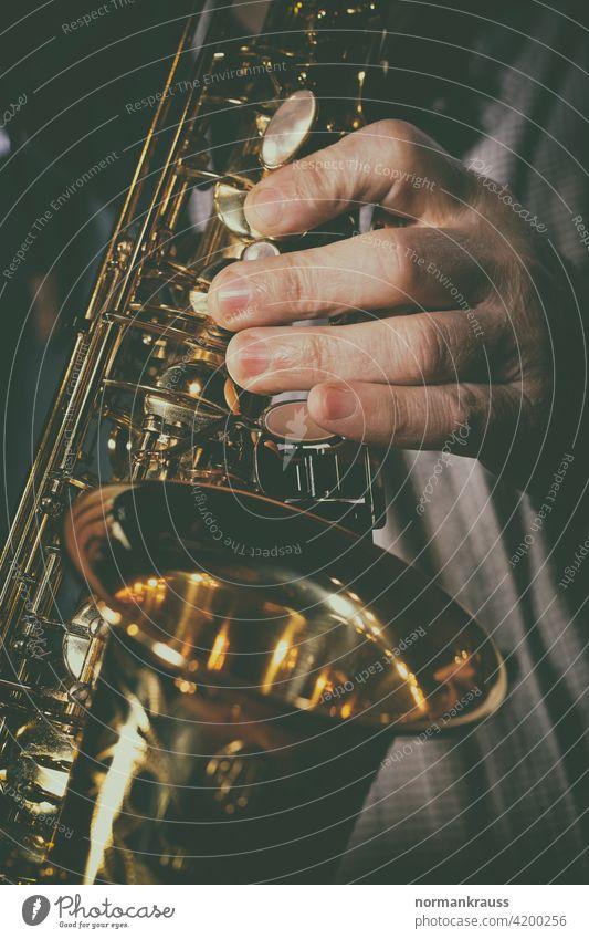 Saxophone and musician Hand Fingers Musical instrument wind instrument tool Musician splendour Gold Brass Woodwind instrument