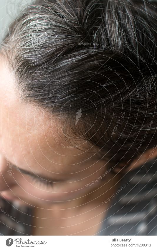 Top of woman's head: gray hair growing in hair care natural grow out dye dye free quarantine silver fresh 40 years old 40 something female wrinkles self care