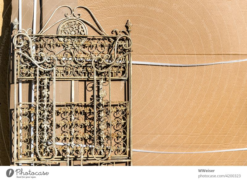 The squiggly old grille leans against a cardboard wall Grating Fence Curlicue Ornament Iron Rust frisky artistic paperboard Sun Light Bright warm rusty Old