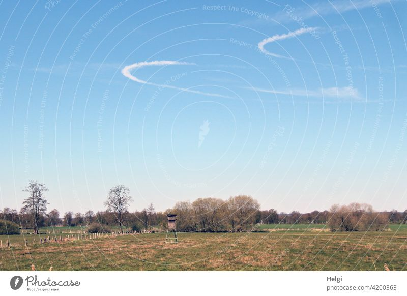 two arc-shaped condensation trails in the blue sky above a meadow with a high seat and trees Landscape Nature Meadow Hunting Blind Sky Vapor trail arched Tracks