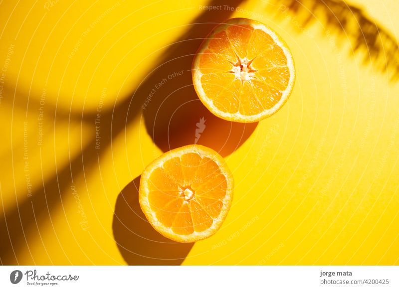 2 oranges in spring with yellow background food fruit freshness juicy vitamin pulp colours nourishment citric fruity refreshment tropical organic fruit stand