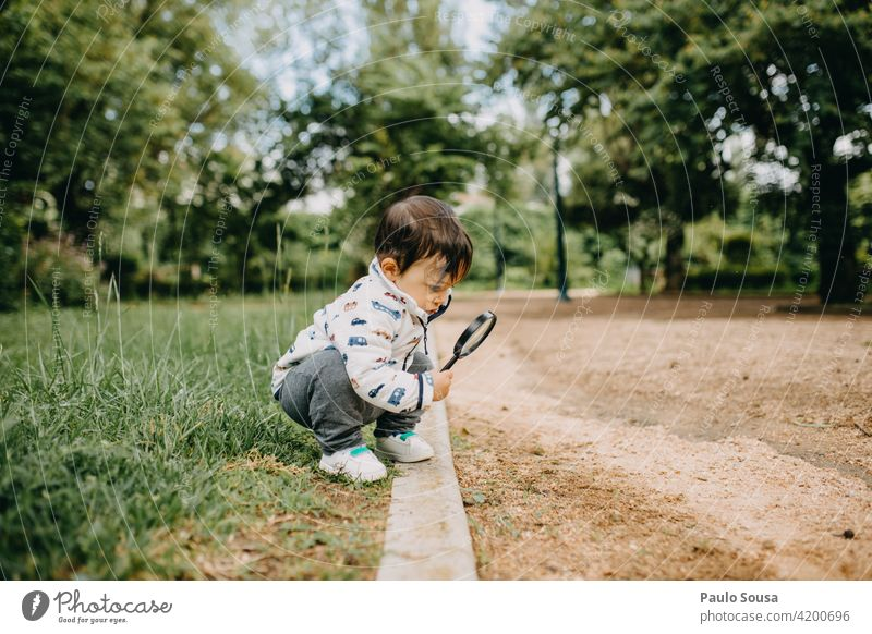 Child playing with magnifying glass 1 - 3 years Caucasian Curiosity Magnifying glass Nature Boy (child) Exterior shot Playing Human being Toddler Joy